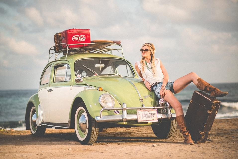 Digitaler Nomade mit Retro-Auto und Hippie-Outfit