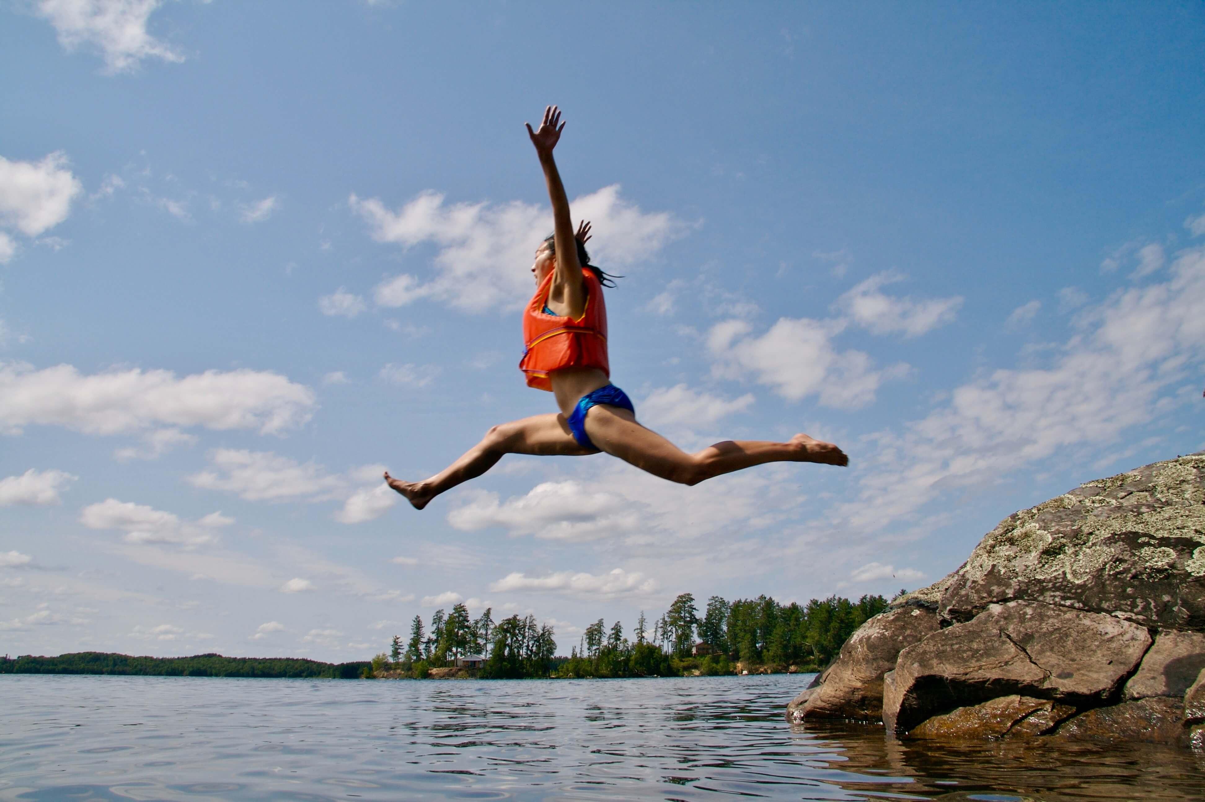 Frau mit Schwimmweste springt in See